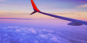 Picture of airplane wing in purple sunset clouds